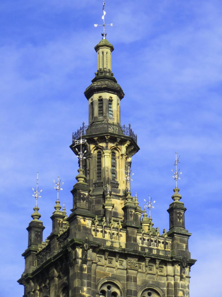 Detail of the church tower with ornate stone work, iron railings and silver finials.
