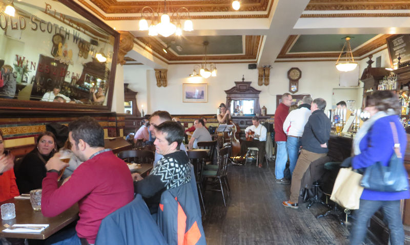 Pub interior with wooden floor, old mirrors, tile work and musicians