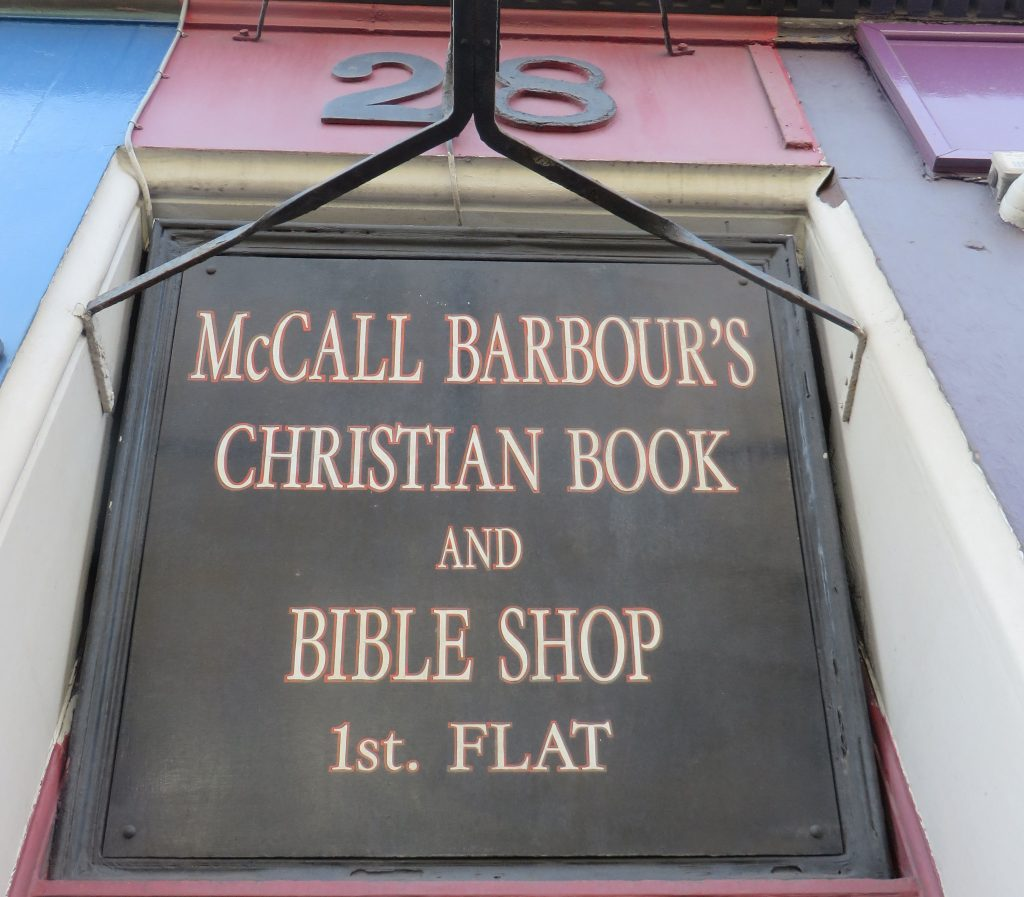 A sign above a door. The sign reads, McCall Barbour's Christian Book and Bible Shop. First flat.