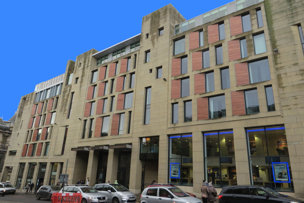 A modern hotel building, built from sandstone with red detailing on the frontage.