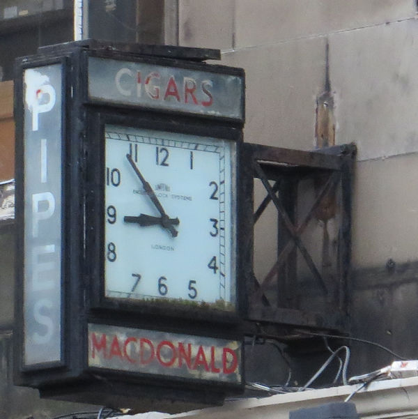 An old square clock attached to the front of a building. The hands are stilled at five minutes to nine