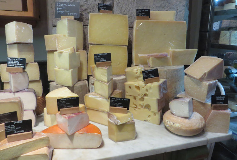 A display of cheeses, stacked high