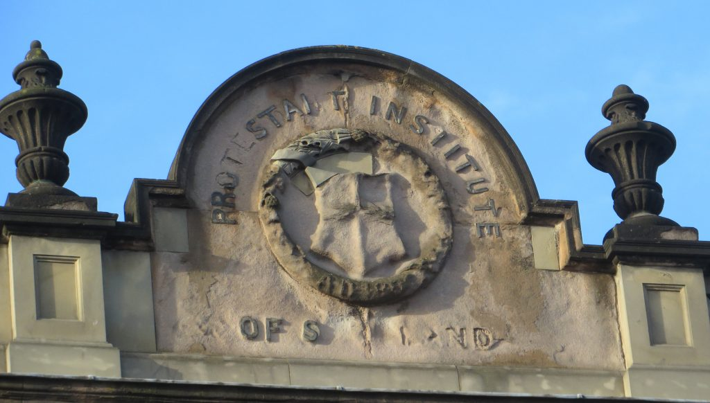 A stone pediment with worn letters reading Protestant Institute of Scotland