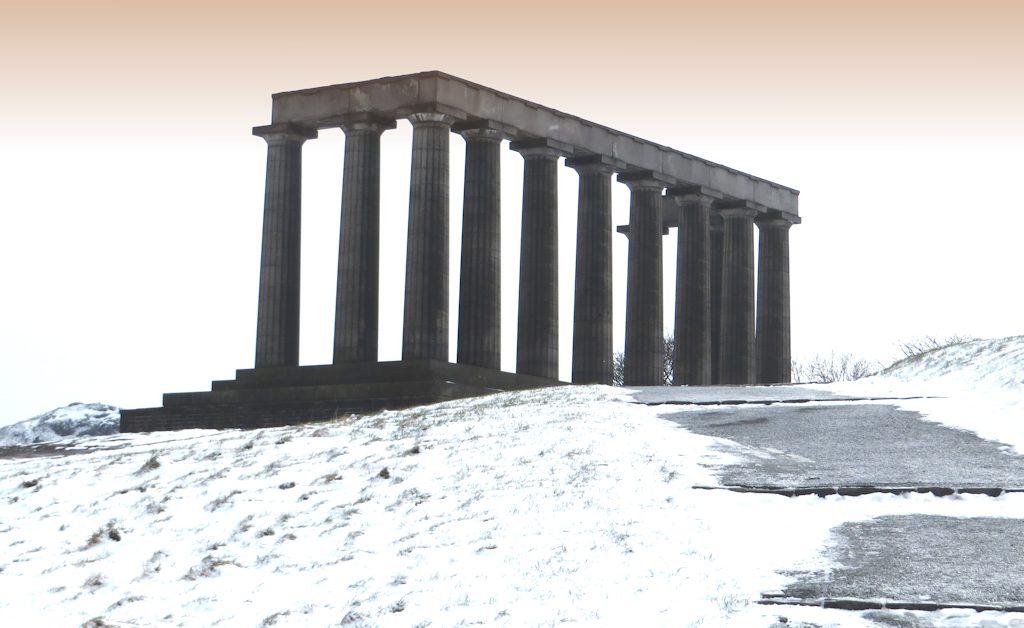 A line of classical Greek columns stand in the snow against a pale winter background