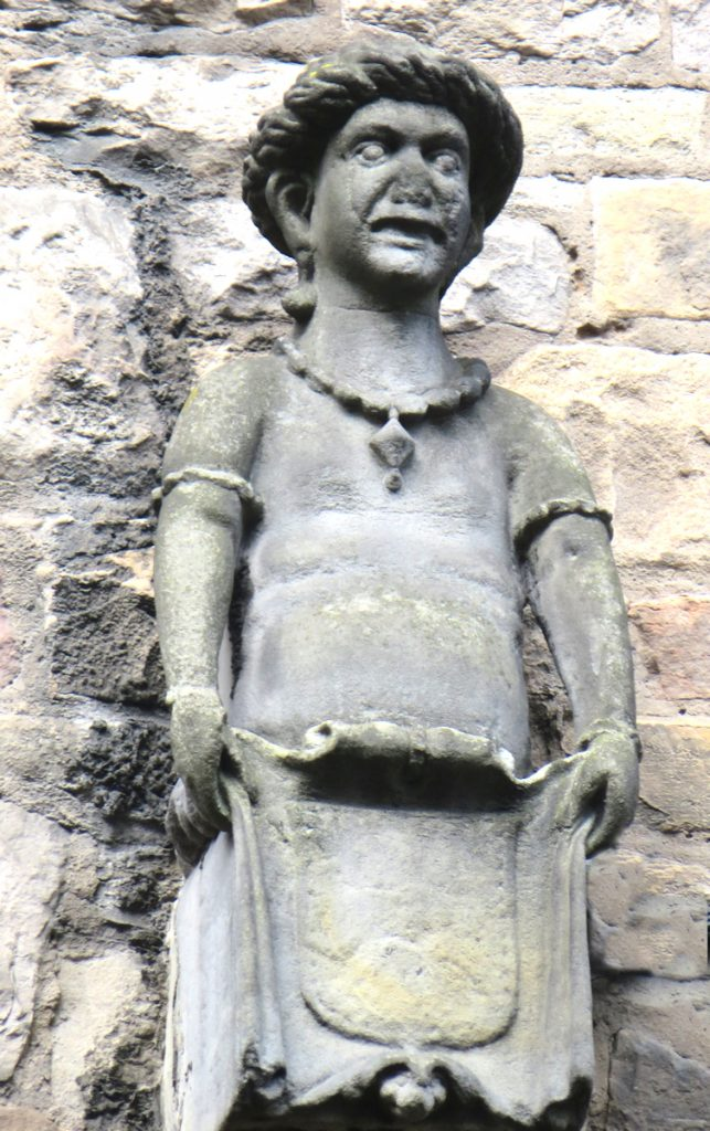 A stone figure, high on a wall.