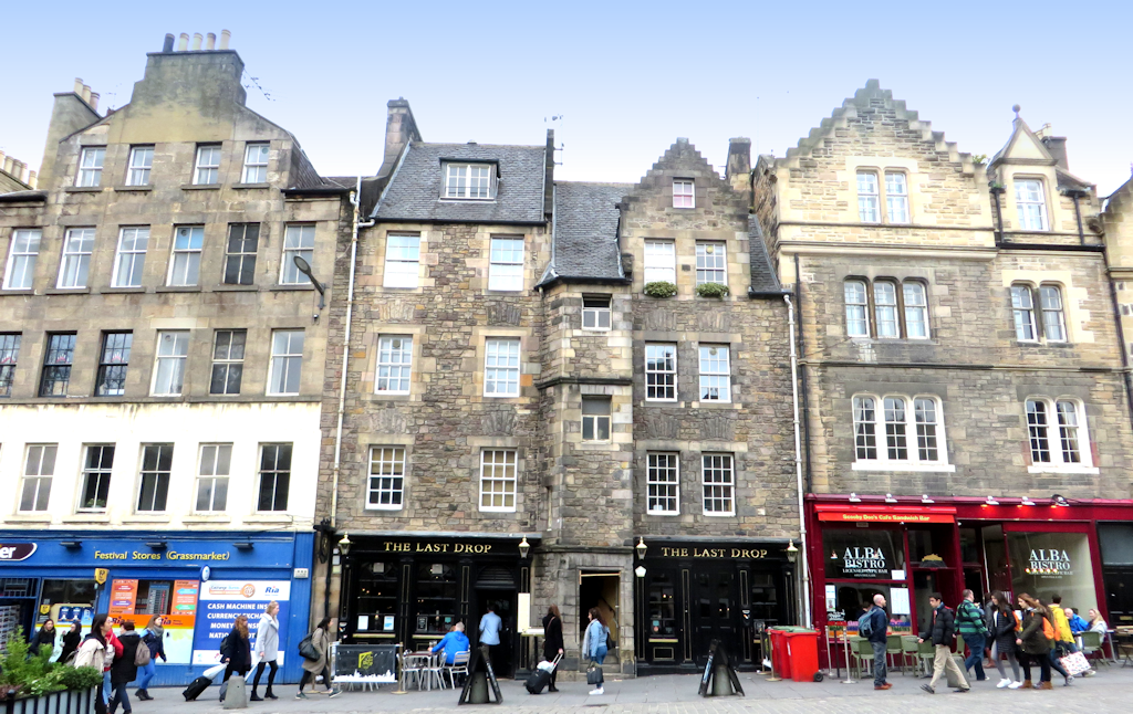 A tall four storey tenement in the Grassmarket. The ground floor is occupied by a public house named The Last Drop Inn.