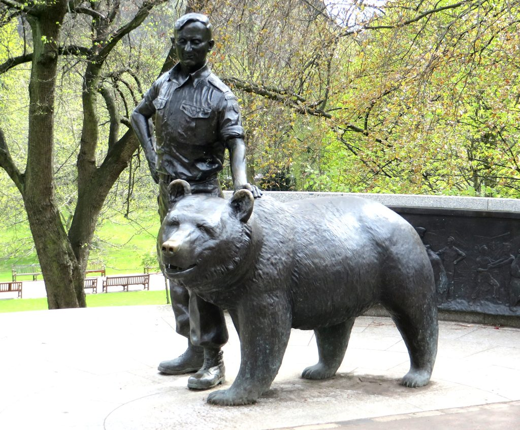 Bronze statue of a bear on all fours walking with a polish soldier