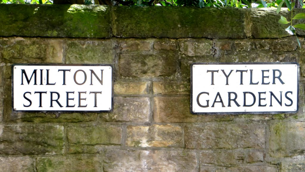 Stone wall with two adjoing street signs. One says Milton Street, the other Tytler Gardens.