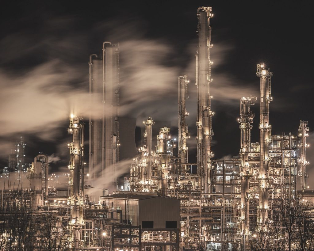 An oil refinery. Many towers covered in lights. Clouds drift through them.