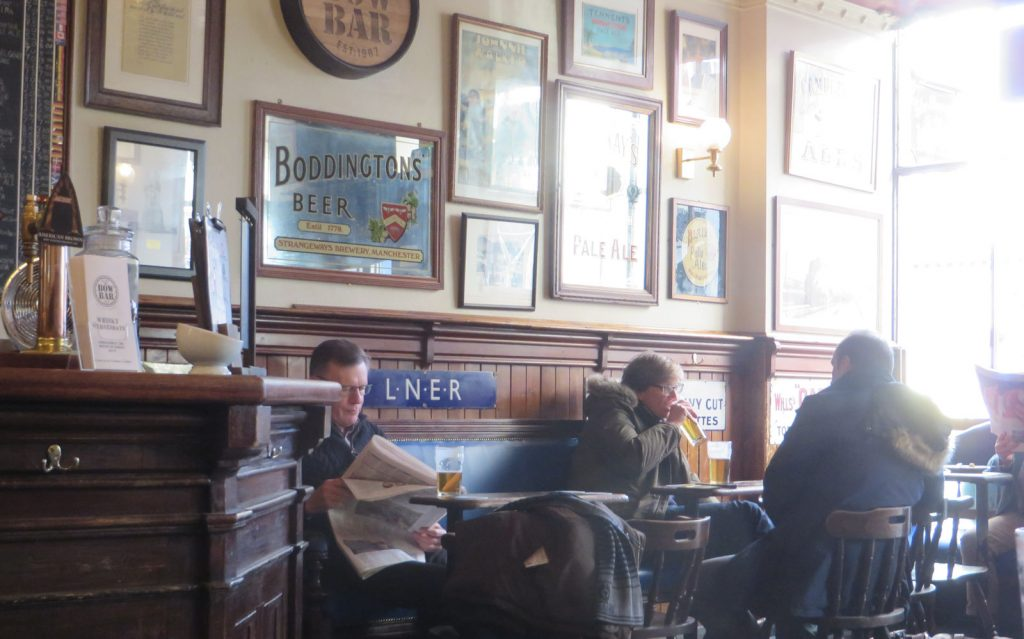 Pub interior with wooden panelling, mirrors and pictures