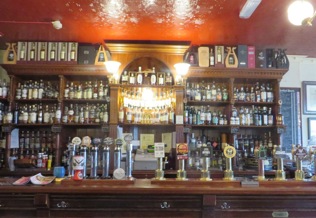 A wood fronted bar with ten beer fonts and dozens of bottles of whisky