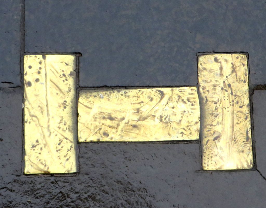 Three Brass plates set in the ground in the shape of the letter aitch