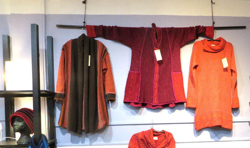 Three knitted tops in vivid oranges, reds and browns