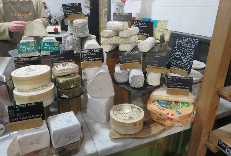 A marble counter with many soft cheeses