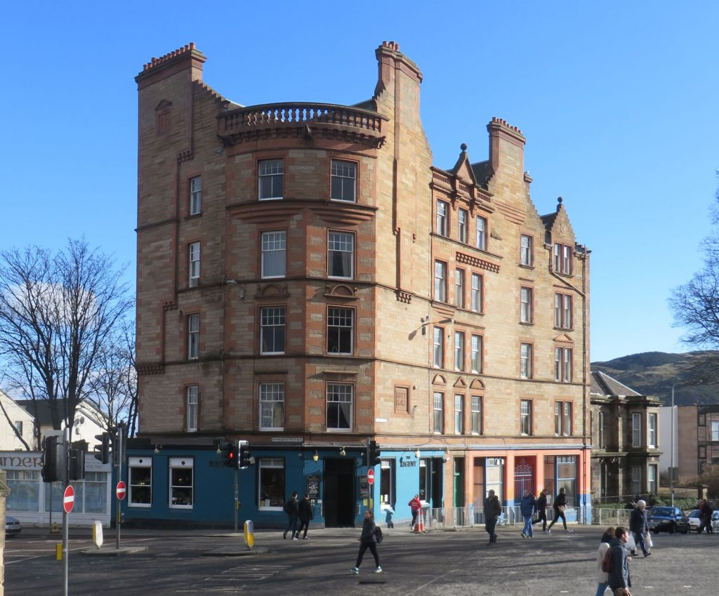 A four storey, red sandstone tenement with a bar on the ground floor
