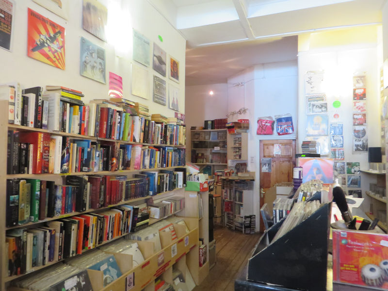 A shop interior with rows of books above rows of Vinyl records