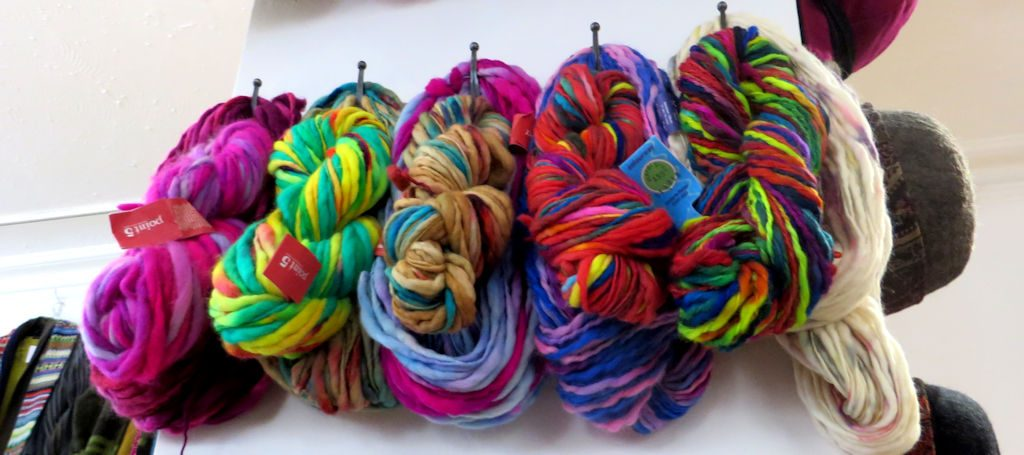 Skeins of multi-coloured wool hanging on a wall