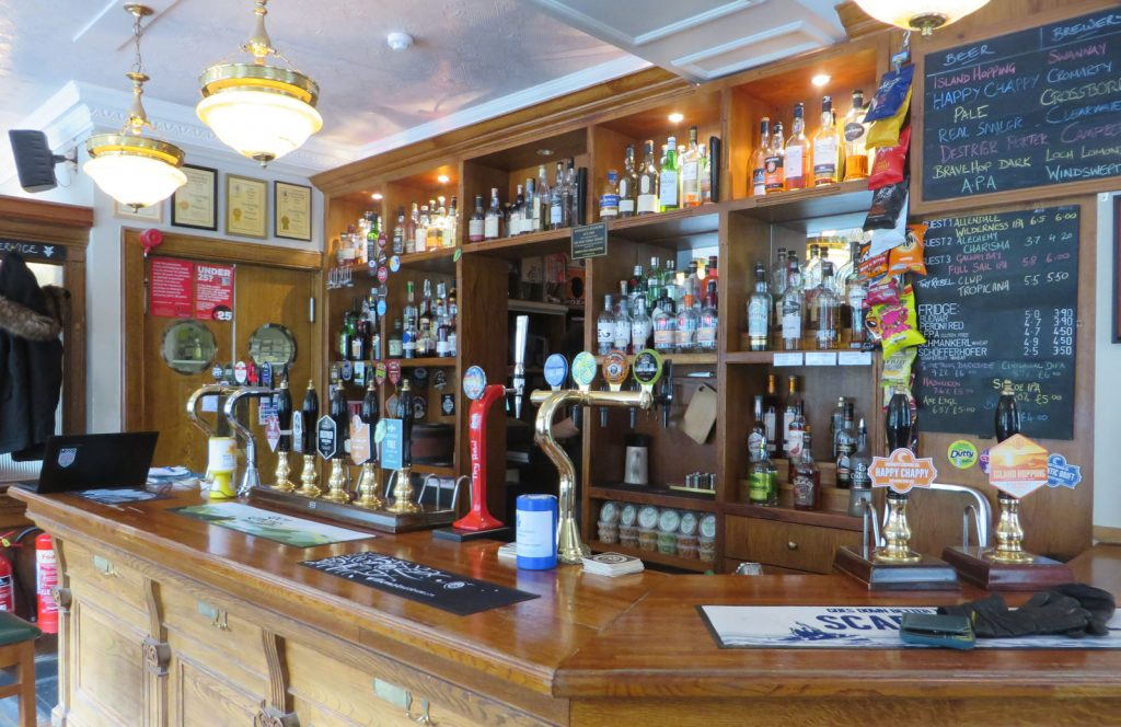 Wooden bar with traditional handpulls, founts, whiskies and beer menus on blackboards