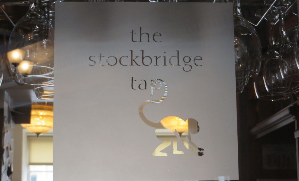 Etched glass screen with the words, the stockbridge tap and a silhouette of a long tailed monkey